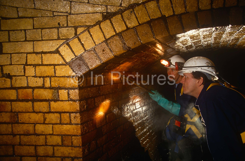 An inspection by the Thames Water Utilities sewer cleaning team looks closely at Victorian-era brick wall linings of the Fleet Rivers Victorian-built storm sewer of Blackfriars, beneath the streets of the City of London, on 19th June 1994, in London, England. Discarded fats from restaurants congeal in sewer networks leading to blocked pipework. Sewer men shovel the deposits and bring them in vats to the surface. In the early 19th century the River Thames was practically an open sewer, with disastrous consequences for public health in London, including numerous cholera epidemics with the The Great Stink of 1858 a turning point. Intercepting sewers constructed between 1859 and 1865 were fed by 450 miles 720 km of main sewers that in turn conveyed the contents of some 13,000 miles 21,000 km of smaller local sewers using 318m bricks, 880,000 cubic yards of concrete and mortar and excavation of over 3.5m tonnes of earth.