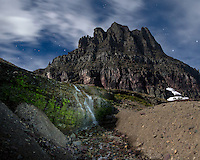 A waterfall is illuminated under the moonlit sky. The peak in the background is the 8,760 foot Clements Mountain.