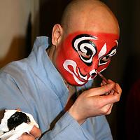 Asia, China, Beijing. Beijing opera performer backstage applying make-up.