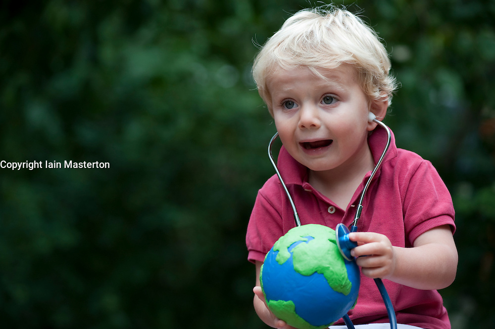 Young boy holding model of planet Earth and checking its health with a stethoscope