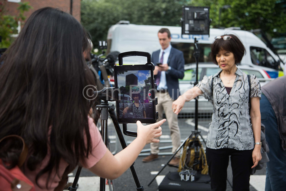 An Asian tv station get ready to broadcast using an iPad below the burned out tower June 16th 2017, London, United Kingdom. Grenfell Tower burned out after a catastophic fire killing more than 58 people. The tower caught fire early Wednesday morning and final casualty figueres may end up to be many more with police not expecting to be able to find and recover all bodies and to find all missing people. No fire sprinkler in place and cheap cladding made with plastic is so far blamed for the ferocious fire.