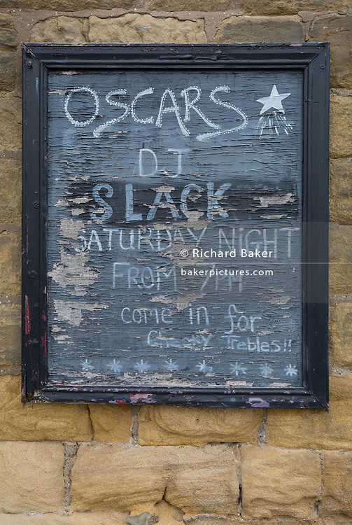 Detail of a peeling and faded pub sign feating its Saturday night entertainment in a Northumbrian town, on 26th September 2017, in Alnwick, Northumberland, England.