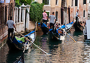 """Gondolas are traditional, flat-bottomed rowing boats which ferry people through Venetian canals. From a peak of 10,000 gondolas 200 years ago, just 500 gondolas now serve Venice. The banana-shaped modern gondola was developed in the 1800s. The left side of the gondola is made longer than the right side to resist leftwards drift at the forward stroke. The gondolier stands on the stern facing the bow and rows just on the right side, with a forward stroke and compensating backward stroke. The oar or rèmo is held in an oar lock, or fórcola, shaped for several rowing positions. The decorative fèrro (meaning iron) ornament on the front can be made of brass, stainless steel, or aluminum, as counterweight for the gondolier standing near the stern. The six horizontal lines and curved top of the ferro represent Venice's six sestieri (districts) and the Doge's cap. Painting gondolas black originated as a sumptuary law eliminating ostentatious competition between nobles. Until the early 1900s, many gondolas had a small cabin (felze) with windows which could be closed with louvered shutters--the original """"venetian blinds."""" The romantic """"City of Canals"""" stretches across 117 small islands in the marshy Venetian Lagoon along the Adriatic Sea in northeast Italy, Europe. Venice and the Venetian Lagoons are honored on UNESCO's World Heritage List."""
