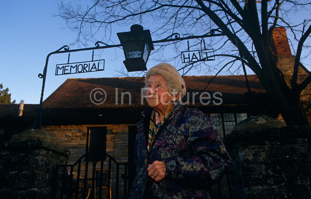 An elderly lady makes her way from her community village Memorial Hall which she has been volunteering this winter morning as part of a charity funds raising event. The lady might be old and frail but her spirit is such that she still finds the time to integrate into community life and remains active despite her years. Walking beneath the wrought-iron sign in Cleeve Prior, Worcestershire, she edges under tentatively to make her way home wearing a quilted coat and her wedding ring on her gnarled hands. A chilly late-morning sun shines across the architecture of the building and this is the look of a lady happy with her morning's activities with fellow parishioners.
