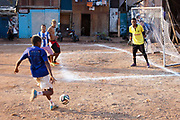 Young men play football on a red earth pitch with wooden favela buildings in the background. Opening World Cup 1014 game, Favela Do Moniho, Sao Paulo, Brazil. (photo by Phil Clarke Hill/In Pictures via Getty Images)