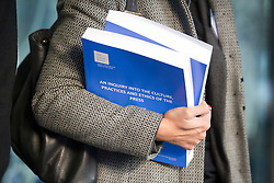 © London News Pictures. 29/11/2012. London, UK. A copy of the Leveso Report being held ouside the QEII centre in London following Lord Justice Leveson's  announcement about his report into the culture and ethics of the UK's press. Photo credit: Ben Cawthra/LNP