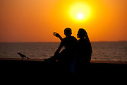 Young Indian couple sit on seawall at sunset at Nariman Point, Mumbai, formerly Bombay, India
