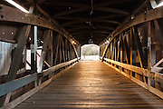 A Burr Arch Truss supports Mecca Covered Bridge (150 feet long), which was built over Big Raccoon Creek in 1873 by J.J. Daniels in historic Parke County, Indiana, USA. Golden sunset light beckons through the far opening.