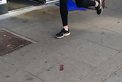 © Licensed to London News Pictures. 13/04/2021. London, UK. A joggers runs past blood stains on the pavement outside Dave's newsagent on Grand Parade, Green Lanes in Haringey, north London following the stabbing of a 16 year old boy. Police were called at 9pm on Monday, 12 April to reports of a stabbing and found a boy with an injury to his stomach. He was taken to a hospital and his condition is critical. Photo credit: Dinendra Haria/LNP