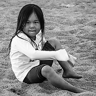 A little inuit girl cleaning the sand on her feet.
