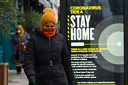 "© Licensed to London News Pictures. 29/12/2020. London, UK. A woman wearing a face covering in north London walks past the government's 'Coronavirus Tier 4 - Stay Home' publicity campaign poster. Many parts of the UK entered the highest level of COVID-19 restrictions on Boxing Day after the mutated SARS-Cov-2 virus continues to spread around the country. The Medicines and Healthcare Products Regulatory Agency (MHRA) is likely to approve a COVID-19 vaccine developed by Oxford University and AstraZeneca this week.  Medical experts have warned that urgent national action is needed to prevent a ""catastrophe"" amid rising rate of coronavirus infection, as hospitals in England are dealing with more COVID-19 patients than during the April peak. Photo credit: Dinendra Haria/LNP"