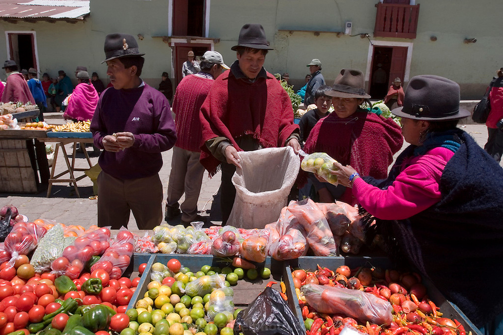Orlando Ayme, 35, (wearing a red poncho), buys some oranges and other fruit from a vendor in the weekly market in Simiatug (his wife, Ermalinda is by his side, also with red poncho). He sold two of his sheep at this weekly market in the indigenous community of Simiatug for $35 US in order to buy potatoes, grain and vegetables for his family.  (Supporting image from the project Hungry Planet: What the World Eats.)(MODEL RELEASED IMAGE)