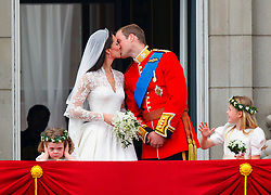 Prince William and his wife Kate Middleton, who has been given the title of The Duchess of Cambridge, kiss on the balcony of Buckingham Palace, London watched by bridesmaids Margarita Armstrong-Jones (right) and Grace Van Cutsem (left), following their wedding at Westminster Abbey.
