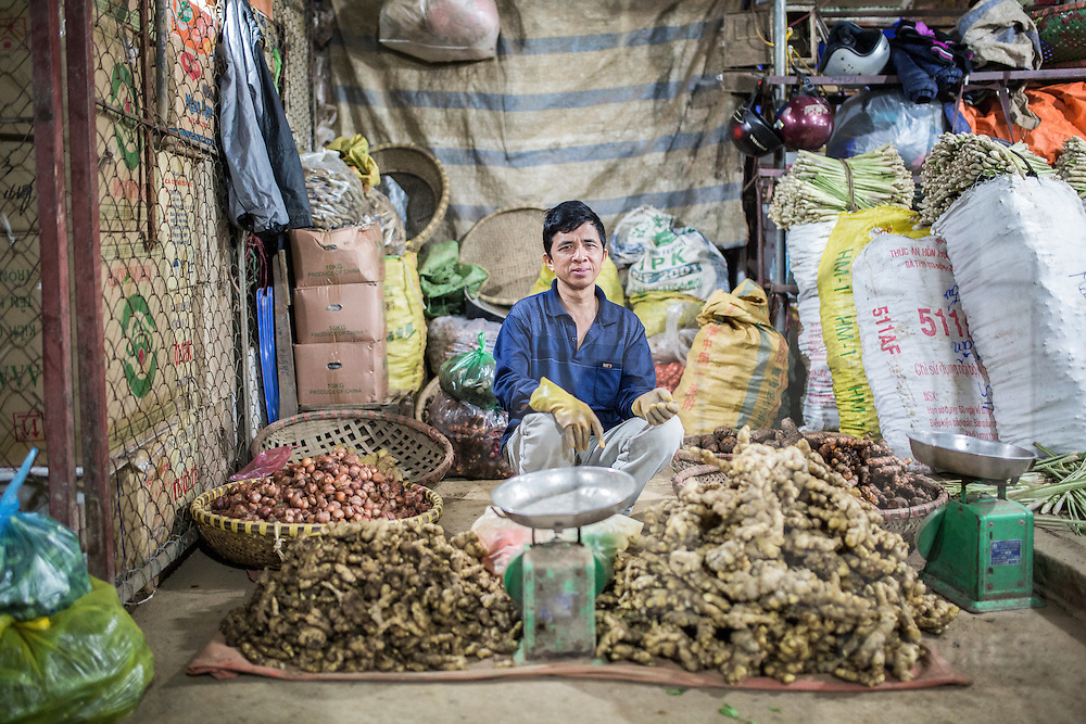 A vendor in Long Bien Market sells dried onions, ginger and other root spices, Hanoi, Vietnam, Southeast Asia