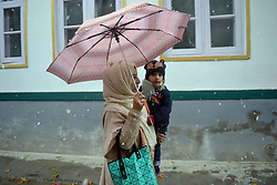 A Kashmiri women along  with child walks briskly holding umbrella amid snowfall in Srinagar, the summer capital of Indian controlled Kashmir. Kashmir witnessed its first snowfall.