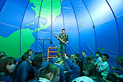 Year 3 pupils take part in a discussion about sustainable development inside a large globe style tent. The workshops are run by Camp Kernow, a Cornwall based organisation teaching sustainable development to primary schools.
