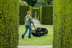 Gardener mowing the 'rondel' at Sissinghurst Castle Garden. Yew hedges surrounding circular lawn