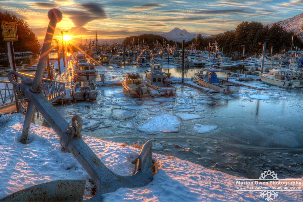 Winter sun sets over boats and pancake ice in Saint Herman Boat Harbor, Kodiak, Alaska.