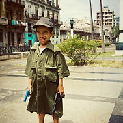 A cuban boy with toy guns and an army shirt standing on the sidewalk in downtown Havana, Cuba.