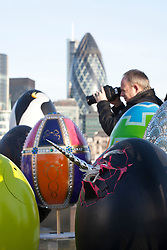 © licensed to London News Pictures. London, UK 20/02/2012. A photogrpher takes pictures of 30 special designed eggs which are positioned together by Elephant Family and Action for Children charities for a photo opportunity in front of Tower Bridge. Photo credit: Tolga Akmen/LNP