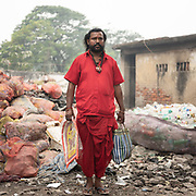 A Hindu religious priest comes to visit the community living in the garbage dump.  A visit to one of the main garbage dump. With 15 millions population in 2019 and growing, the city of Calcutta is a typical case of expansion through uncontrolled urbanization.