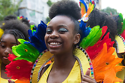London, August 28th 2016. A girl in the procession smiles of the camera during Family Day at Europe's biggest street party, the Notting Hill Carnival.