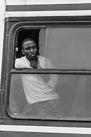 A passenger waits on a bus while waiting for the Save police convoy, Save River Bridge, Inhambane Province, Mozambique