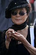 LIVERPOOL, ENGLAND, UNITED KINGDOM: Yoko Ono shines a 'love torch' at a photocall on the steps of St Luke's Cathedral under one of her controversial images which she has donated to the 3rd Liverpool Biennial, the UK's largest contemporary arts event which commences on September 18, 2004 and runs until November 28. The image is being used to promote the Biennial...Photograph © Colin McPherson, 17/09/04..Tel. +44 (0)7831 838717..Email: cmc1964@aol.com