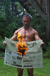 naked man reading a newspaper that has caught on fire