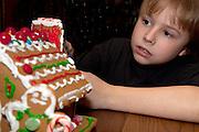 Boy age 10 decorating Christmas gingerbread house. St Paul Minnesota USA