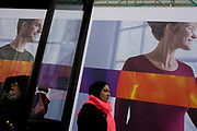 Large models appear on a construction hoarding for clothing retailer Uniglo in central London. We look up from a low angle to see shoppers passing-by including a Muslim lady wearing a pink scarf and others in more western dress. The models in the background advertise the Uniglo brand in a forthcoming shop on Oxford Street. There is a strong theme of diagonal lines and rectangles helped by the dark upright from a bus stop shelter.