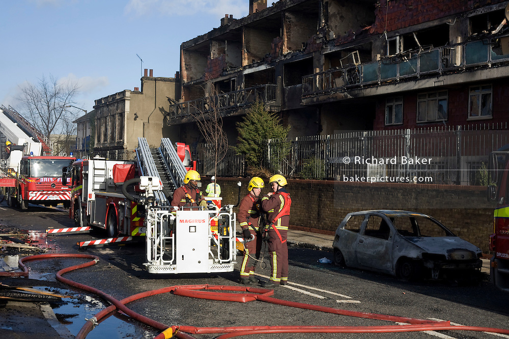 Fire fighters in the aftermath of an inner-city estate fire in south London. About 310 people were forced to leave their homes after the fire engulfed a wooden structure under construction in scaffolding at Sumner Road and Garrisbrooke Estate, Peckham, London at about 0430 AM. It spread to two blocks of maisonettes and a destroyed a pub. More than 150 firefighters tackled this unusually large and ferocious fire which injured ten people, including two police officers who received hospital treatment for minor injuries.  .