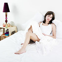 woman lying on a white bed