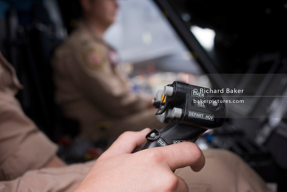 US Navy pilot grasps cyclic in the cockpit of a Sikorsky MH-60R helicopter at the Farnborough Airshow. ..The MH-60R is the U.S. Navy's newest and most advanced multi-mission helicopter, designed for anti-submarine and surface warfare (ASW/ASuW). Secondary missions include: Search and Rescue, anti-ship surveillance and targeting, communication relay and medevac/vertical replenishment. The Sikorsky-built helicipter with integrated avionics and mission systems by Lockheed Martin.