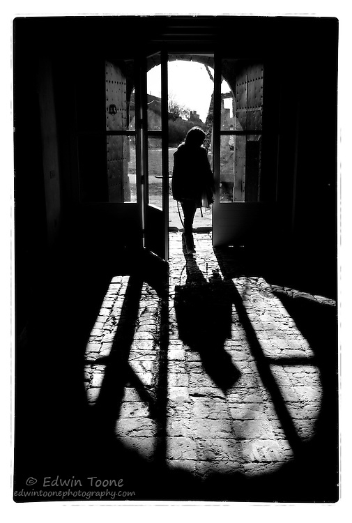 A silhouette of a woman as she enters the arched door of a Spanish masia.