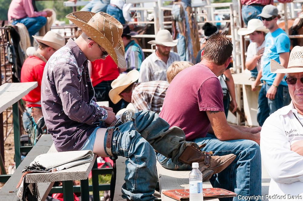 Sunday afternoon, a young cowboy prepares for a bull ride by taping up his thigh.