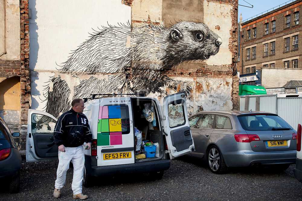 Roa is a Belgian street artist renowned for his giant black and white animals which can be found on walls and shutters in varying states of decay. Here seen is a beaver character in a parking lot on Hackney Road. There are also a few Rats and Birds which reside on shop shutters along Brick Lane.<br /> <br /> Street art in the East End of London is an ever changing visual enigma, as the artworks constantly change, as councils clean some walls or new works go up in place of others. While some consider this vandalism or graffiti, these artworks are very popular among local people and visitors alike, as a sense of poignancy remains in the work, many of which have subtle messages.