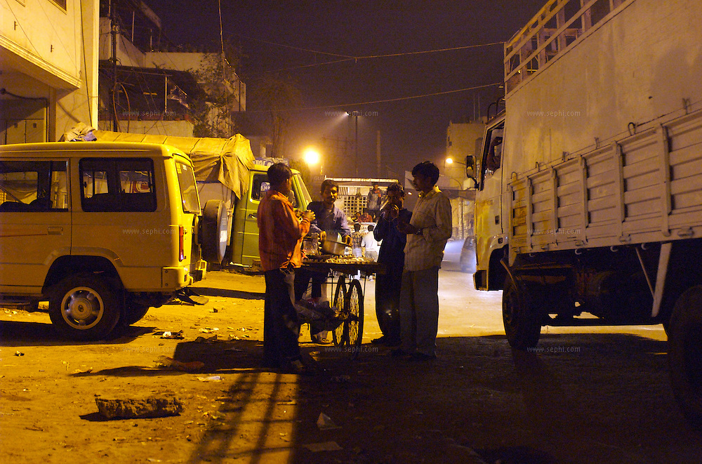 Close to midnight, on a street otherwise busy with heavy traffic, people grab a quick night bite from a passing 'anda-walla' selling eggs and egg sandwiches. New Delhi, India