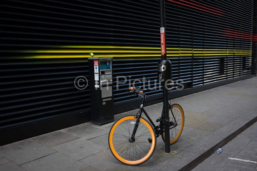 Courier bike is locked up on post near yellow and red stripes on office building side street. Propped up against a lamp post which as a cigarette butt and gum receptacle and near a parking payment unit, the bicycle has bright orange wheels and handlebars. On the wall in the background are yellow-sprayed stripes that go off into the distance. A discarded bottle of water lies in the gutter and a coffee cup has been wedged into the air conditioning grill.