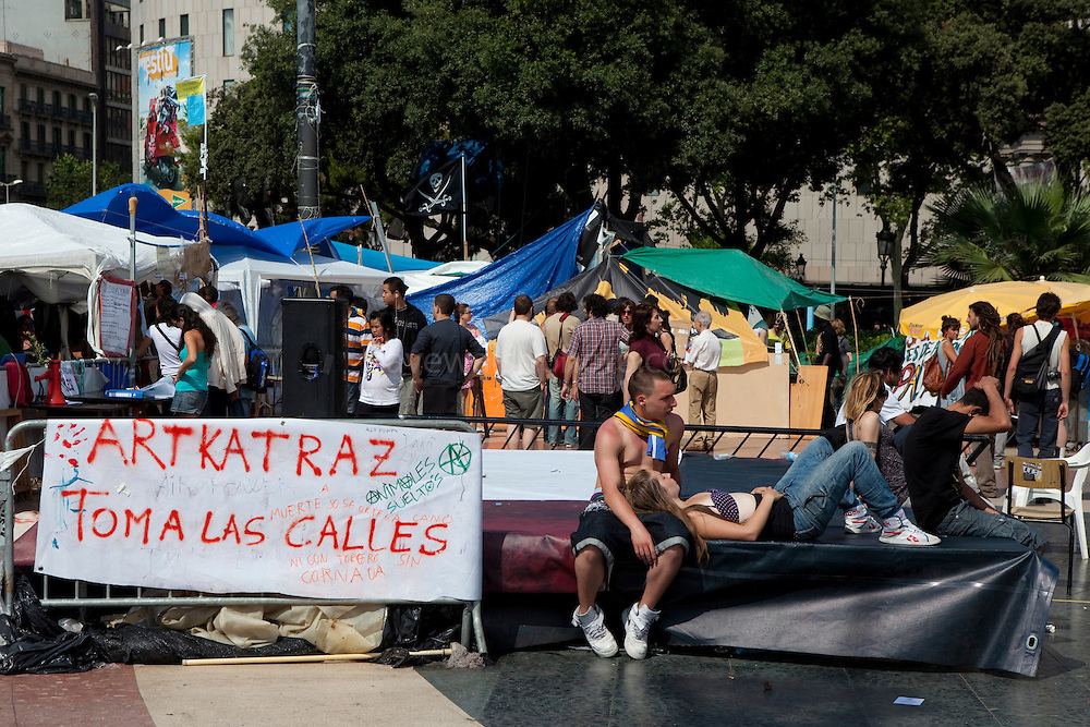 """People enjoying afternoon sun at the antigovernment protest camp at Placa de Catalunya, Barcelona, Spain. Banner reads: Artkatraz takes to the streets"""". The square has been relatively quiet since police attacked and beat protestors on May 27 2011."""