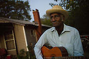 """BESSEMER, AL – OCTOBER 8, 2011: Blues legend Henry """"Gip"""" Gipson, 90, strums an acoustic guitar in front of his home before his weekly performance in his backyard juke joint.<br /> <br /> After an altercation with the KKK in the 60's rendered his left hand badly broken, Gipson's method of guitar playing had to change. """"I had to crowd the strings,"""" Gipson said, describing the method that he adopted. Today, Gipson operates Gip's Place, one of few true remaining juke joints in the country. """"Music don't care no color,"""" Gipson said. """"And that's why I love blues, because blues deals with a story to tell you."""""""