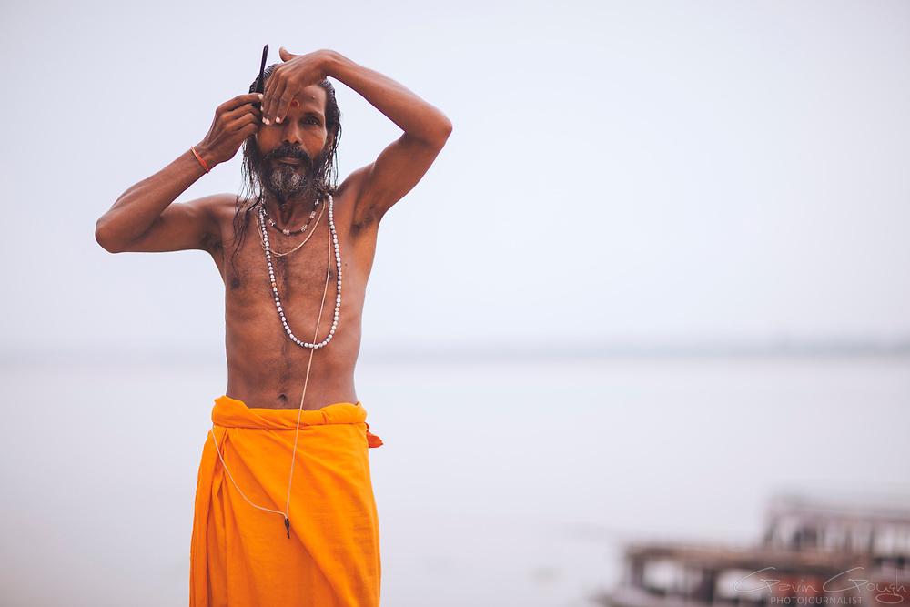 A Hindu Sadhu wearing an orange lungi combing his hair after his morning meditation and bathing routine, Assi Ghat, River Ganges, Varanasi, India