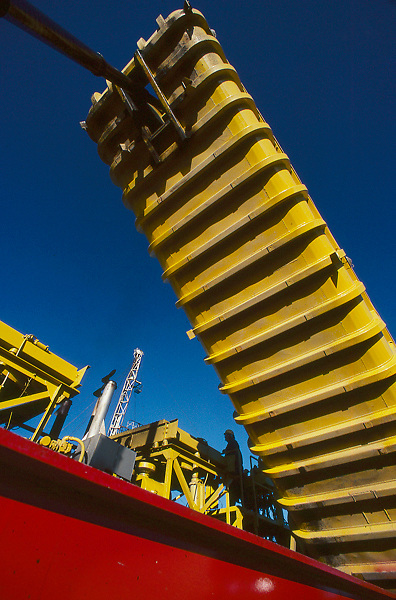 Stock photo of an oilfield truck emptying sand at well head site