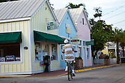 Riding a bicycle past shops in the Bahama Village section of Key West, Florida.