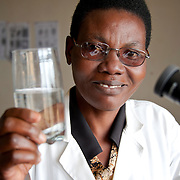 Antoinette, a lab technician at Kisaro Community Clinic, holds a glass of safe drinking water in Kisaro Sector, Rulindo District, Rwanda.