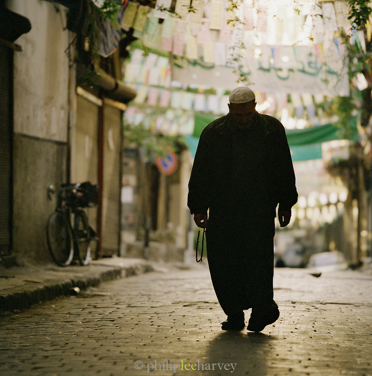 An eldely man walks through the quiet streets in the early morning of Damascus, Syria
