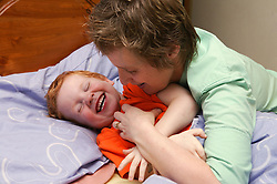 Single parent tickling her young son at bedtime,