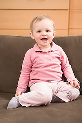 Baby girl 18 months old sitting on sofa laughing