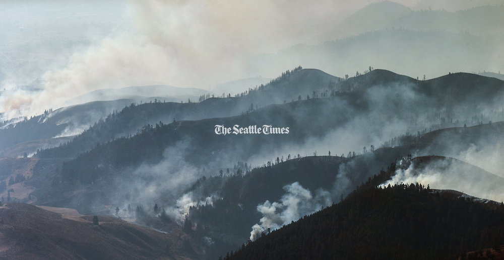 The hills of the Methow near Winthrop and Twisp are filled with wildfire and smoke in central Washington as seen from a helicopter Thursday August 20, 2015.<br /> <br /> Bettina Hansen / The Seattle Times