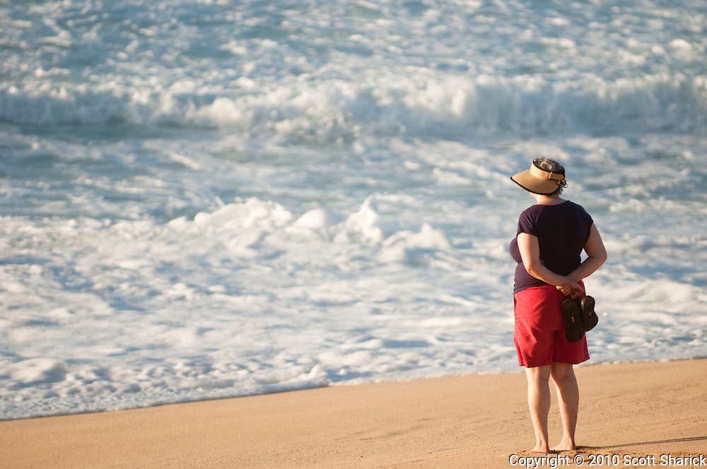 A female tourist stands at the waters edge watching the waves.